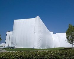 Large building covered in white fumigation tent.