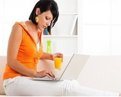 Woman sitting on a couch researching on her laptop.