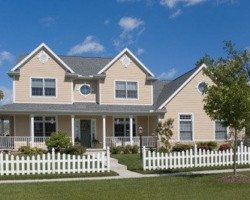 Beige residential home with white picket fence.