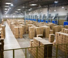 Warehouse full of stacked cardboard boxes.