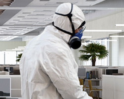 Man in personal protective equipment in an office.