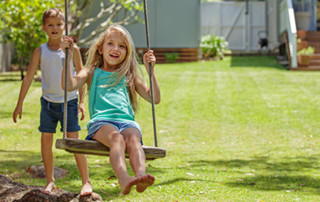 Kids Playing on Swing in Back Yard