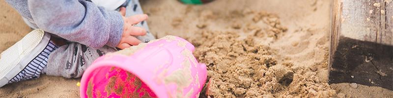 Child playing in sandbox on playground